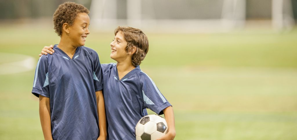 Two elementary age boys are standing together after the soccer game with a soccer ball.