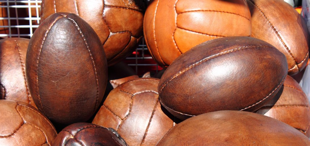 Leather soccer and rugby balls sold in a market stall